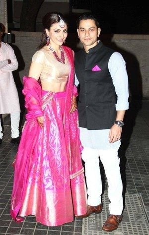 Soha Ali Khan's Reception - Soha and Kunal seemed to have gone for a relatively understated, minimalist look - refreshing from all the heavy pieces that you normally see at receptions! Soha wore a beautiful pink Sanjay Garg lehenga while Kunal Khemu wore a black Nehru jacket with a khaki white shirt, white pants and a bit of matching pink pocket square to match his new bride. The brown shoes were a nice touch too! Indian celebrity wedding #thecrimsonbride