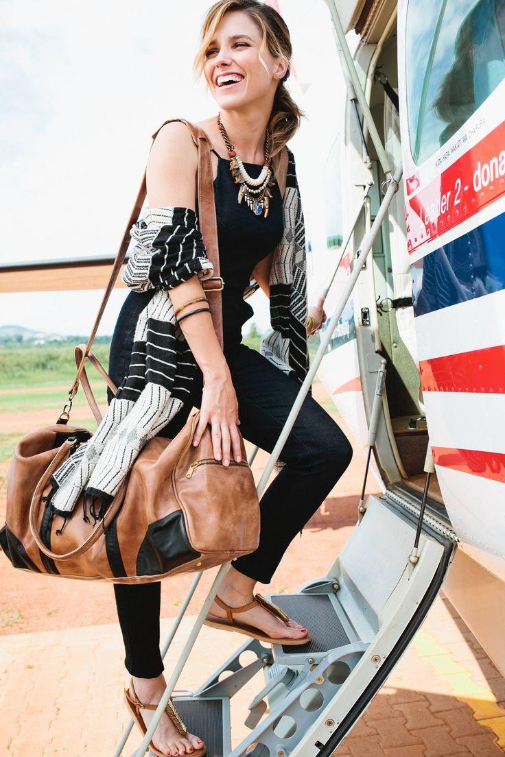 Sophia Bush and Sseko Designs in Uganda. Black wanderlust shawl, weekender duffle bag, and Mojave T-straps by Sseko Designs.