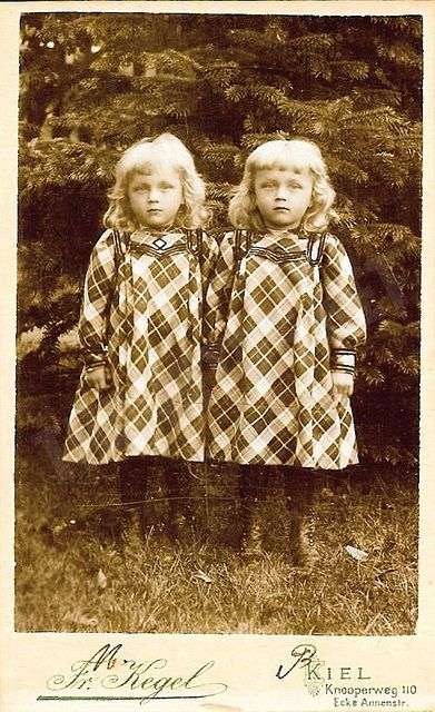Twins. If yoy notice the outfits. They are almost identical. The girl on the left has a diamond on the front of the dress. Maybe mom needed to know who was who?