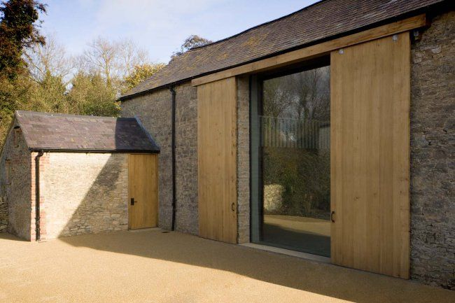 modern barn conversion with glass full length window behind untreated oak doors | Oxfordshire Farm Phase 1 || William Smalley Architects in collaboration with James Gorst Architects