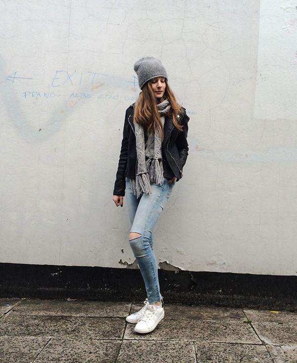 Street style look com jaqueta de couro preta, calça jeans e tênis branco.