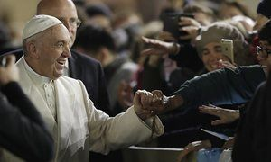 Pope Francis holds hands with people after mass in the Vatican
