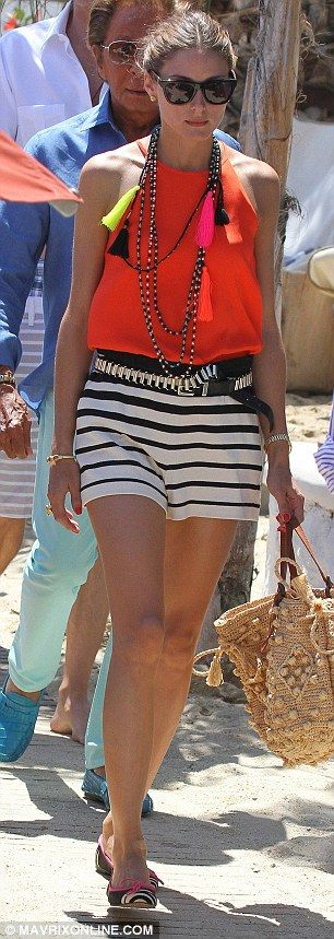 Style maven: Olivia looked chic in monochrome shorts and an orange halterneck, but managed to leave the sticker on her zebra-print pumps