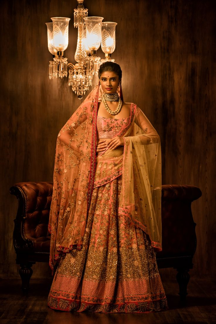 Pretty in pink, A coral tulle lehenga with contrasting flamingo pink and deep red borders, this lehenga has delicate floral embroidery with resham rosettes all over. The lehenga is paired a flamingo pink cholee completely done in antique peeta jaal work, and the look is completed with a contrasting beige tulle dupatta and a matching head veil with antique jaal embroidery. #bridal #trends #bridal2017 #bridalfashion #bridaldress #weddinglehenga #pink #lehenga