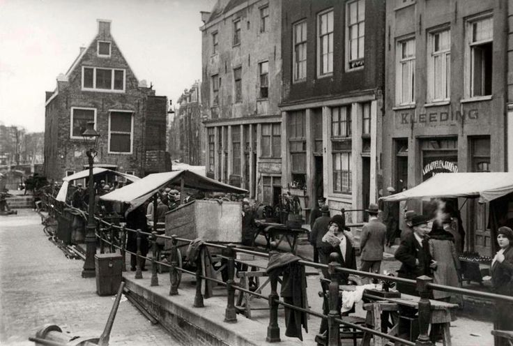 1932   Jodenmarkt aan de Jodenbreestraat.   Tegenwoordig is in het scheve pand Café de Sluyswacht gevestigd.
