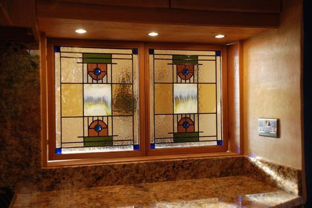 Traditional stained glass opening hatch from kitchen to lounge, the enamel centers created to match a personal collection of the clients artworks.