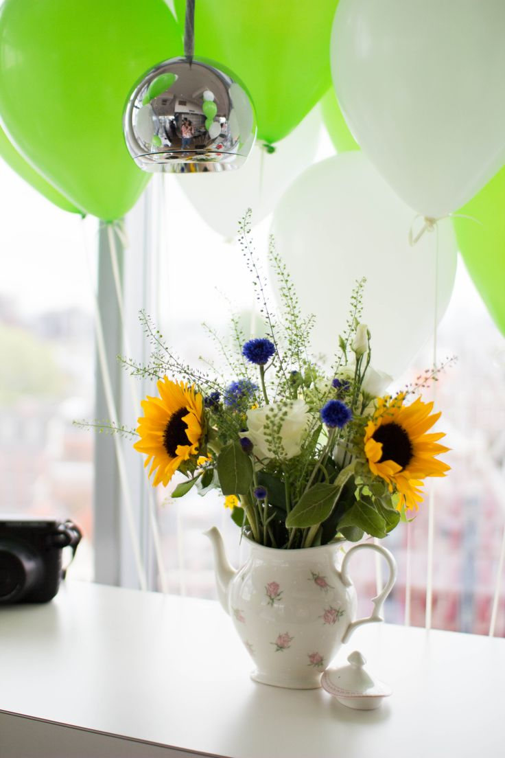 Fill up a teapot as a vase with flowers used in a teablend like sunflowers, cornblossoms and white roses