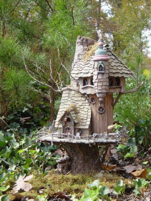 This little treehouse that sits atop a stump has great architecture.  I especially love the shingled roof!  :)