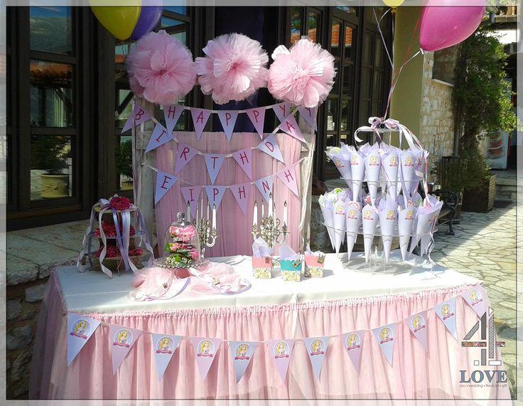 Το welcome είναι διακοσμημένο με ροζ pom pon και λουλούδια. Λουλούδια φυσικά είναι τοποθετημένα και στο τραπέζι μαζί με τα χωνάκια και τα ζαχαρωτά -Concept stylist Μάνθα Μάντζιου