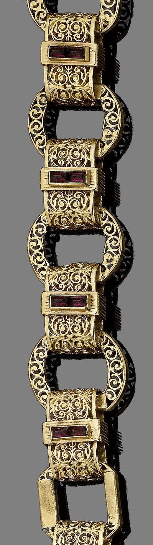 A late 19th century gold and garnet fancy-link bracelet.  Designed as a continuous row of pierced discs, connected by similarly engraved rectangular links of foliate design, centrally-set with two pyramidal-shaped garnets, French assay marks, lengths 17.0cm