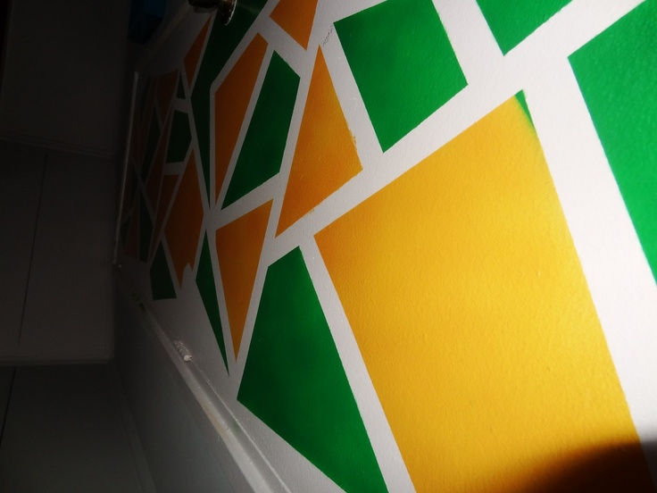 Mosaico en pared. 1. Pega cinta adhesiva en tu pared haciendo formas (triangujos, cuadrados) 2. Pinta con distintos colores encima de la cinta 3. Espera que la pintura se seque 4. Retira la cinta adhesiva y te va a quedar asì :D  PD: Lo blanco que se ve en la foto es donde estaba la cinta antes, para que se entienda mas :)