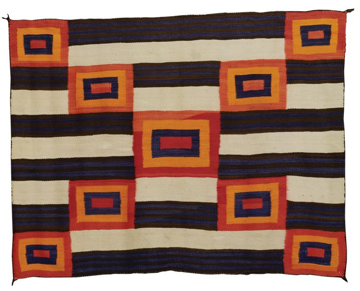 Navajo Blanket - Softly woven, in natural ivory and dark brown, and aniline blue, red and orange, with a stylized Chief's Third Phase design, composed of nine concentric squares overlaying a banded and striped ground.