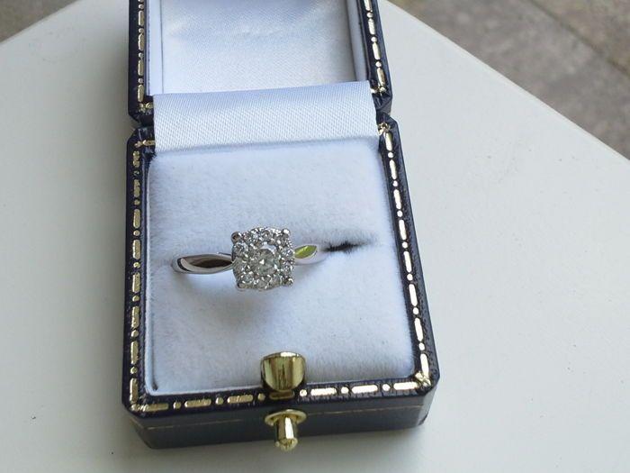 18 karaat witgouden ring met centrale diamant van 025 ct totaal 055 ct  Deze 18 karaat wit gouden ring is stijlvol gesmeed. De ring is gezet met een heldere briljant geslepen diamant van 025 ct. Daar omheen is een rand van 10 diamanten gezet van elk 003 ct. Totaal 055 ct. Een bijzonder sieraad. Afmeting bovenkant 7mm. Gezet met: Diamant 1 x 025 ct briljant geslepen  G-H/ VVS 10 x 003 karaat in de rand briljant geslepen H/VVS Totaal 055 ct. Merken Symbool 750 schild Ringmaat 1725/54 Gewicht…