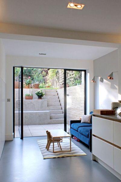 Milton – Blick von der Küche durch Glasschwenktür auf einen neuen Außenbereich mit Betonstufen zum Garten.   – kaoutar boughaba