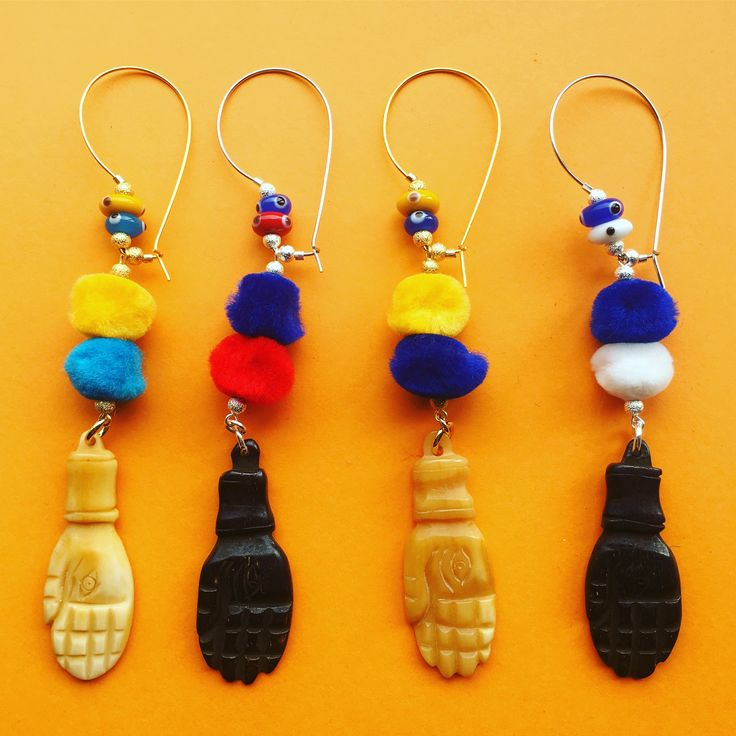 We got that Friday feelin with our pompom party here  - new #danalevy evil eye pompom hamsa hand hoop earrings
