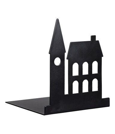 Zwart. Een boekensteun van metaal met het silhouet van gebouwen aan één van de zijkanten. Afmetingen 12x12x14 cm.