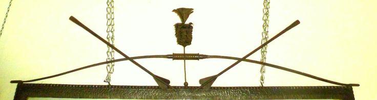 Zeveneken Sint Sebastiaan, metalen bolpanache + 2 gekruiste pijlen in een boog (in de kantine)