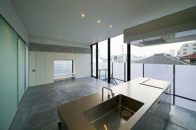 先ほどのキッチンを別の角度から。 後方の壁から突き出るレンジフードもピッカピカの特注ステンレス。