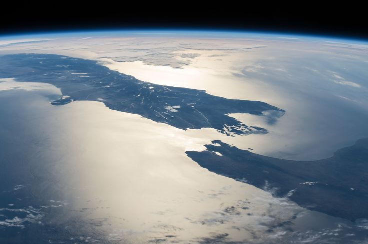 New Zealand in Sunglint February 23, 2015: In this panorama taken from the International Space Station (ISS), the Sun's glint point highlights the details of Cook Strait, between New Zealand's North and South Islands. Astronauts looking west towards the setting Sun were able to see this high-contrast detail even though the center of the glint point was 1,000 kilometers (600 miles) away from the ISS. The sunglint shows Wellington Bay—where the capital city is located—opening onto Cook Strait…