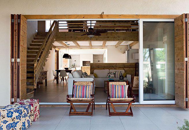 A dona da casa brinca com o filho, Antônio, na cozinha integrada ao jardim pela abertura da porta de correr com caixilho de madeira e vidro. Projeto do arquiteto Thiago Passos