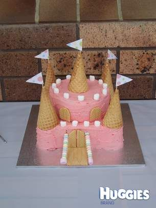 This was made from a square cake on the bottom and a small round cake on top. The turrets around the outside are made from a stack of jam filled packet biscuits. It was then covered in pink butter cream icing. The idea came from a women's weekly magazine.