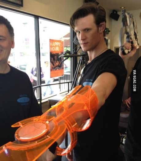 Dr. Who (Matt Smith) trying on an Omni-Tool (Mass Effect). Where was this, Bioware HQ? Somebody's even holding a Phalanx replica just over Matt's shoulder.