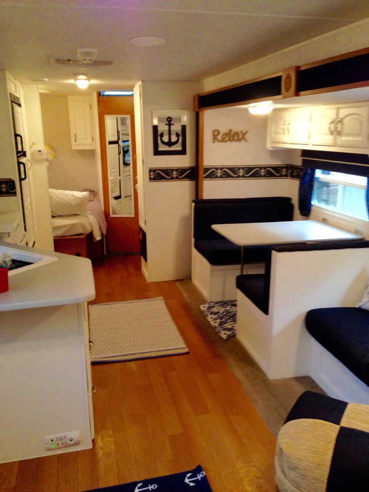 White cabinets. Navy and white booth. Wood laminate floors. Fitted print rug under booth. Beach. Nautical. Camper. Camper renovation. Camper remodel