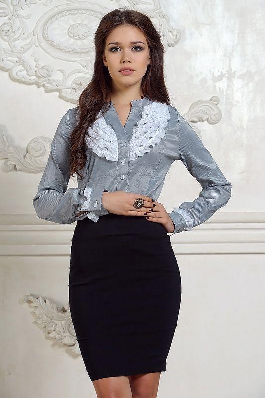 Серая классическая рубашка с рюшами, средней длины. Вырез горловины высокий, стоечка, вокруг шеи. Рукав модели втачной, полуоблегающий, в окончании на широких манжетах. Модель приталенного, облегающего кроя, застегивается на мелкие пуговицы. Рубашка серебристого цвета в мелкую черную полоску. П