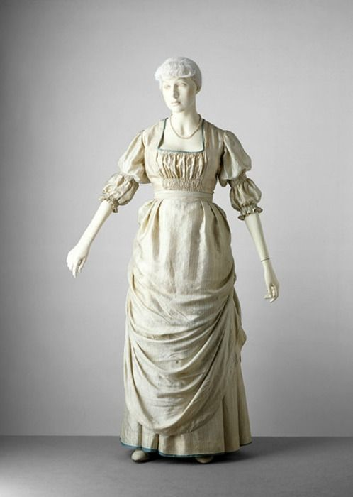 1885 The V Was made & worn by the wife of Sir Hamo Thornycroft a sculptor Interested in the dress reform movement & conceived the dress in accordance w/ the movement's principles so it didn't restrict waist & arms. It fits a natural figure & is cut fairly full w/ smocking at the back & front The sleeves are elbow-length puffs smocked & gathered 2 reflect historical styles. Skirts consist of an overskirt draped w/ tapes gathered up & an underskirt mounted on a white cotton lining & tied back