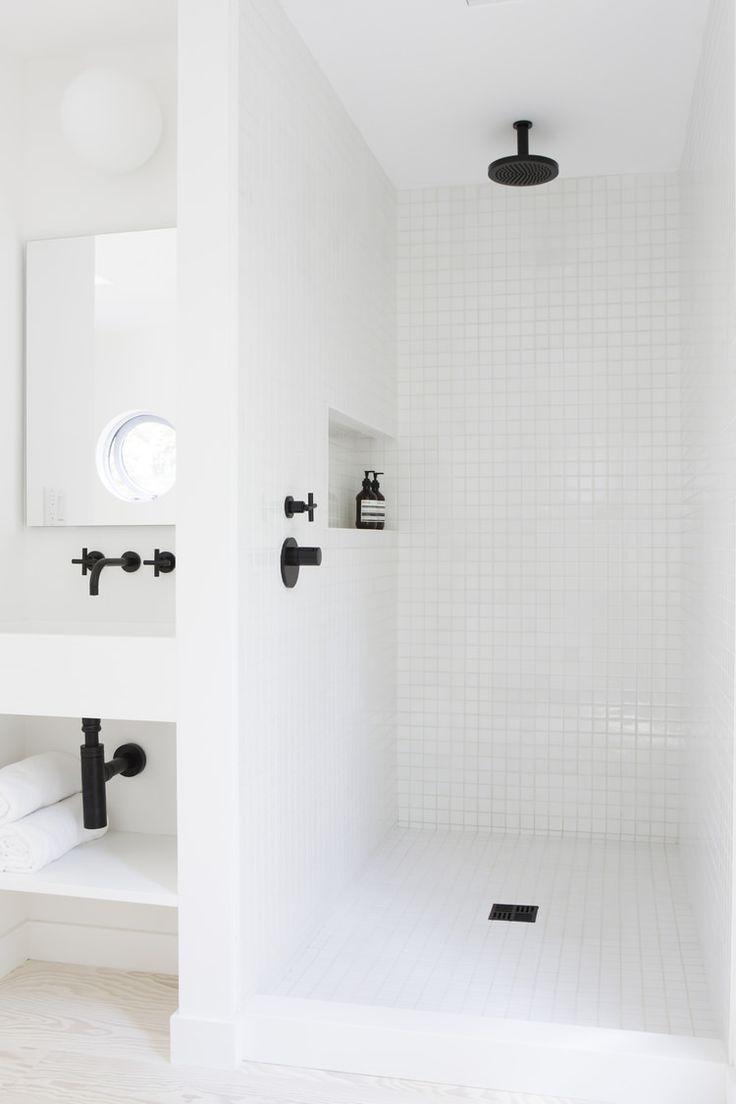 マットなブラックの水栓金物を用いた白いタイル張りのバスルーム