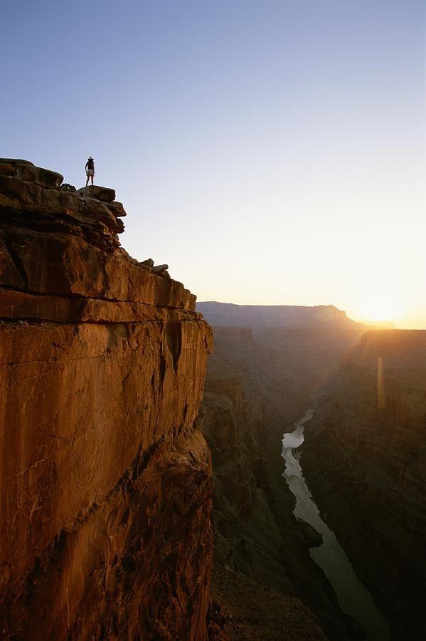 A hiker surveys de Grand Canyon from atop Toroweap Overlook at Sunrise