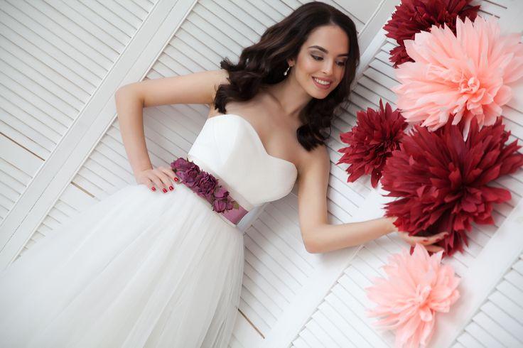 Белое пышное платье из еврофатина, украшенное поясом цвета марсала. Топ с вырезом сердечко. Декор из лгущих бумажных цветов красного и розового цветов. Приобрести платье можно на нашем сайте: www.fairytaleforyou.com