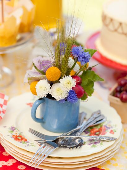 A very colourful place setting. I would be delighted to have a mug of flowers to take home :)