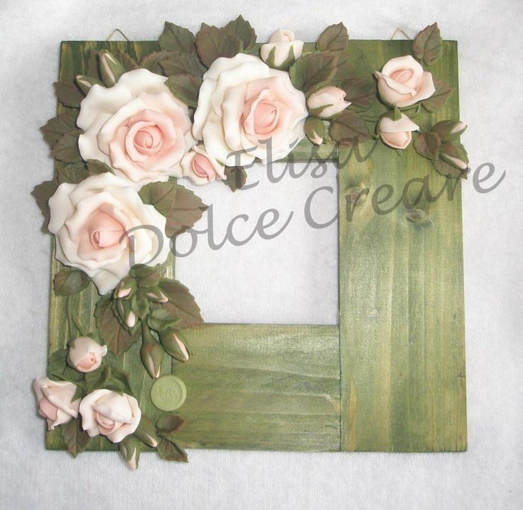 Cornice in legno tinteggiato in verde con buco con rose rosa in pasta di mais