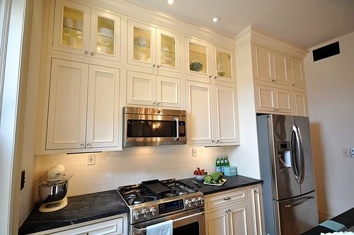 I love the tall, stacked cabinets. And the recessed lights. And the shiny appliances. And the whole thing.