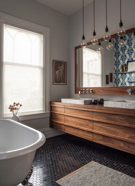 Wood vanity, big wood mirror, black floor tile, white bath, coloured tile on back wall.