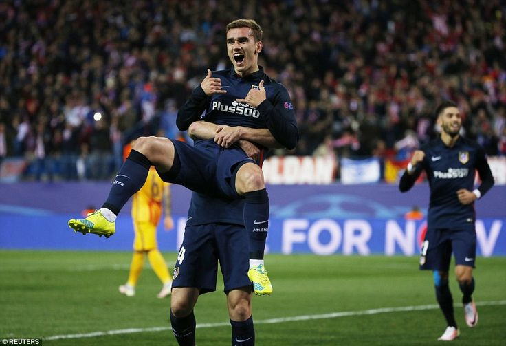 Atletico Madrid forward Antoine Griezmann is lifted in the air during the celebrations after heading the hosts into the lead