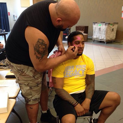 Big Show helping Jimmy Uso with his war paint before a WWE live event