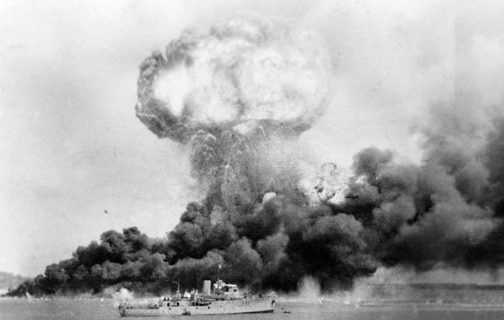 The explosion of an oil storage tank and clouds of smoke from other oil tanks, hit during the first Japanese air raid on Australia's mainland, at Darwin on 19 February 1942. In the foreground is HMAS Deloraine, which escaped damage. From Wikipedia.