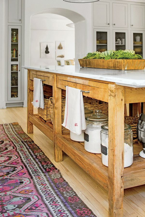 A weathered pine table is topped with marble and functions as an island to give the kitchen a strong center point that both visually grounds the all-white room while also standing up to the wear-and-tear of a busy household.
