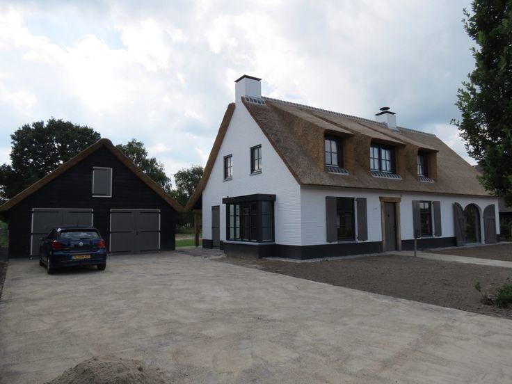 Witte boerderij villa met rieten dak en bijpassende garage.