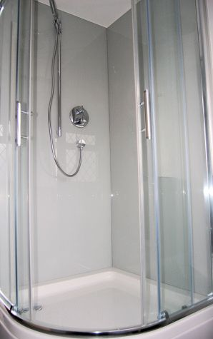 Photograph of Opticolour dove grey glass bath panels which have been drilled to accomodate shower attachments...