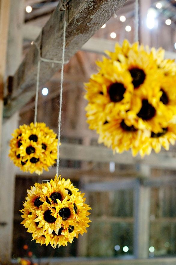 Sunflower Pomander Ball in Yellow with Hanger    Create this beautiful sunflower pomander decoration.  We lined up a row of our votives and hung our sunflower kissing balls at different lengths over the candles using jute cord.  Once we lighted the candles, it became a beautiful backdrop for a head table, or for pictures. All flower and supply sugg