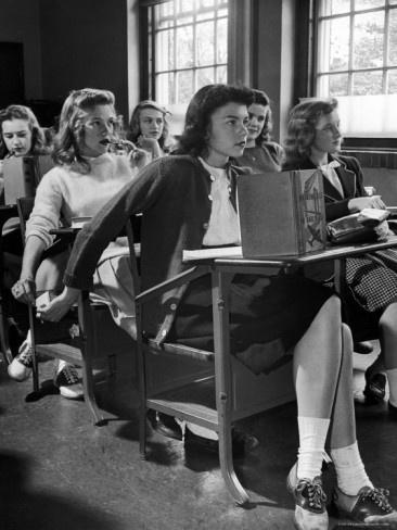 Highschool-Schüler, der der Mitschülerin, die hinter ihrem Fotodruck von Nina Leen sitzt, eine Nachricht übergibt