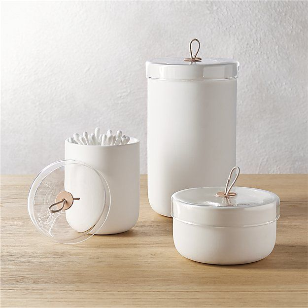 Shop ventura white ceramic canisters.   We wanted clean, natural, unfussy (yet upscale) canisters for the bath––so we designed these.  White ceramic demi cylinder with rounded base, handmade glass lid and natural leather pull.  Pure and simple perfection.