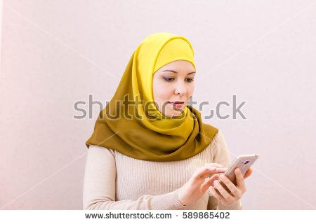 Portrait of a smiling beautiful muslim woman texting with her smartphone while sitting on a couch at home