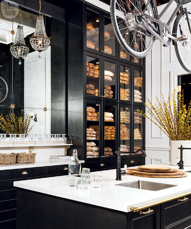 4 Reach for the sky—Stacked glass-fronted floor-to-ceiling cabinetry accentuates the kitchen's height and drives home the boulangerie look – especially when filled with delicious breads from Ontario-based Ace Bakery.