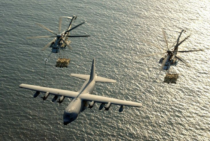 A pair of Super Stallion helicopters receive fuel from a KC-130 Hercules while transporting Humvees over the Gulf of Aden