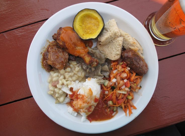 """South Africa has its own version of """"soul food,"""" and it's markedly different from America's soul food. Pictured here, clockwise from top: a variety of spaghetti squash, dumplings (steamed bread), sausage, chakalaka (spicy vegetable relish), mieliepap (ground maize), samp (dried corn kernels) and beans, lamb stew, roasted chicken, and mogodu, or tripe, in the center."""