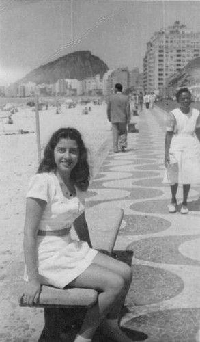 """PRAIA DE COPACABANA - 1946 - A fotografia de hoje foi enviada pelo prezado comentarista Gustavo Lemos, a quem o """"Saudades do Rio"""" agradece. A moça sentada no banco da Praia de Copacabana, defronte ao Copacabana Palace, é a mãe dele. Podemos ver a Pedra do Inhangá ainda chegando até a Avenida Atlântica. Na calçada da praia vemos ainda uma típica babá das décadas de 40/50, toda uniformizada, e um pedestre de terno. - Fotolog"""